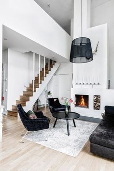 Black and white decor is just so great. It looks sleek, sharp, and very modern. The fireplace and wooden staircase add a homey vibe to this living room too!