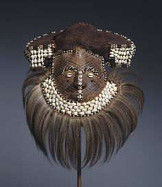 Africa |  Mwaash aMbooy Mask from the Kuba people | ca. late 19th or early 20th century. | Bark cloth, leather, pigment, shell, hair, beads, fabric