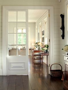 I just love this so much.. dark wood floors.. French doors dividing space.. white beadboard simplicity