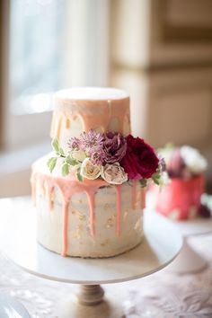 Rustic wedding cake with drizzled frosting and flowers