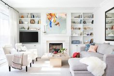 Chic living room features a white limestone fireplace tucked under a pink, orange and blue abstract art piece flanked by built in shelves lined with tchotchkes and a flat panel tv as well as cabinets adorned with bronze knobs.