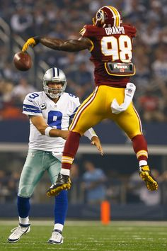 Tony Romo Photos Photos - Brian Orakpo #98 of the Washington Redskins tips a pass thrown by  Tony Romo #9 of the Dallas Cowboys in the second quarter on October 13, 2013 in Arlington, Texas. - Washington Redskins v Dallas Cowboys