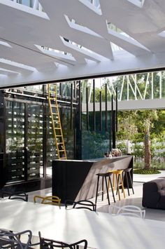 Spanning one wall of the space is a vast glass-fronted wine cooler. A bright yellow ladder leans against the fridge, providing access to bottles on the upper shelves, and adding an accent of colour. Pic via Dezeen