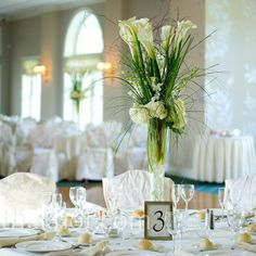 Tall vases filled with long-stemmed white calla lilies, hydrangeas, dendrobium orchids and bear grass.