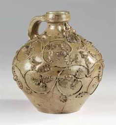 A GERMAN BROWN SALTGLAZE STONEWARE GLOBULAR BARTMANNKRUG   CIRCA 1540, COLOGNE, POSSIBLY MAXIMINENSTRASSE WORKSHOP   The swelling body applied with a grooved loop handle, the neck with a bearded mask above moulded oak leaves, acorns and birds above branches