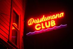 A glowing neon sign invites patrons into the Dedemona Club in Astoria.