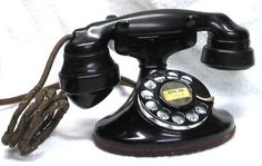 """This is the typical phone of the art deco era, though it doesn't represent art deco style. It was introduced in 1933 and continued production well into the 1950's with slight changes in color and an updated F1 receiver. Shown on this model is the original E1 receiver with the popular """"spit cup"""" on the receiver, which is made of bakelite."""