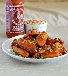 Sriracha Garlic Wings  Serves 4  Ingredients  3 pounds chicken wings, tips removed and wings and drummettes separated 5 cloves garlic, minced 1/4 cup Sriracha 1/2 cup ketchup 1/4 cup soy sauce 2 tablespoons honey 2 tablespoons sesame oil 1 scallion, green parts chopped or thinly sliced 1/4 cup chopped peanuts (optional)