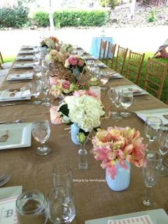 www.designsbyhemingway.com. Our  burlap linen designed table with manzanita  branches , sea shells, blue mason jars, shades of pink garden roses, hydrangeas, anemones, parrot tulips. Designed at Kualoa ranch over looking China Man's Hat! Designs by Debbie Hemingway. Designs by Hemingway. Hawaii wedding florist & event decor. Honolulu, Hawaii