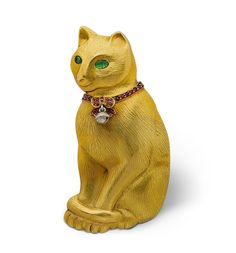 Boucheron cat brooch, 1910. Chased gold, with emerald eyes, a ruby set collar, and a silver bell. Paris. Via Wartski.
