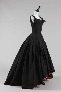 A Pierre Balmain black faille ball gown, circa 1950, with woven white on black label 'Pierre Balmain, Paris, soie naturelle' the flamenco-style graduated hem edged and part lined in bright pink silk faille, boned integral corset, decorative buttons to front, gentle fold to decollete trimmed with a bow, the skirt with graduated bands of pleats, layers of pink tulle petticoats, bust approx 86cm, 34in, waist 61cm, 24in