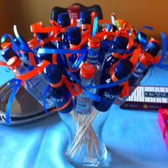 Adult party favors. Hot glue skewers to the back and tie with opposite color ribbon. Guests can break off the skewers and take bottles home. (This is a University of Illinois themed party, hence the color scheme)