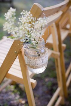 """Bands of burlap around Mason jars, tied off with lace, and filled with baby's breath to fashion """"pew"""" markers."""