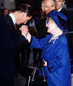 Prince Charles kisses the Queen Mother's hand as she arrives at the Royal College of Music in Green Park, 1993