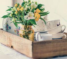O caixote de frutas serve de apoio para pratos, pires e xícaras. O vasinho dá bossa à composição