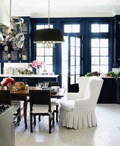 A Windsor Smith kitchen - navy, whites, windows, wingback chair  in the dining area