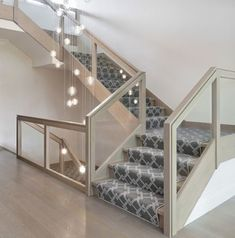 For a dramatic statement upon entry, A-List Interiors and Brooklyn lighting design company Shakuff created a cascading light fixture with hand-blown glass spheres that hangs in the open staircase. Connecting the basement to the second level, the staircase Staircase Railings, Modern Staircase, Banisters, Staircase Design, Staircase Ideas, Staircases, Contemporary Stairs, Stair Design, Modern Entryway