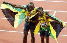 Jamaica's Usain Bolt (L) and his compatriot Yohan Blake hold their national flag after finishing first and second respectively in the men's 100m final during the London 2012 Olympic Games at the Olympic Stadium August 5, 2012