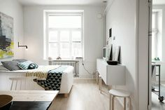 white bedroom with pops of color on bedding and artwork