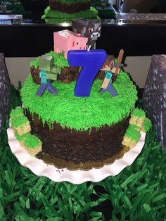 Minecraft theme cake Store bought cake accented with frosting grass, brownie bites, rice crispy squares, and a zombie (of course).