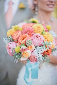 Pink, coral, yellow, with billy buttons, peonies, dusty miller, and what are those green honeycomb flowers? Maybe hydrangea. Love the light blue ribbon to bring out tones in leaves.
