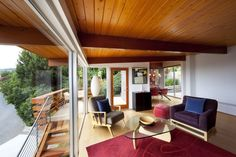 Architecture, Picturesque Living Room With Thick Glass Walls Completed With Two Armchairs And A Red Rug On The Floor Also Ceiling Arranged With Large Woods: Beach House with Traditional Wooden Decor and Stylized with Modern Furniture