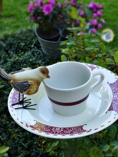 Bird bath and feeder made from decorative bowl, matching mug, and upside down glass vase