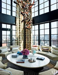 A terrace was enclosed to create the family room, where Deniot devised the brass-and-copper light fixture and the bone-top cocktail table that can be raised to dining height electronically; the curtain fabric is by Christopher Farr, and the carpet is by Tai Ping.