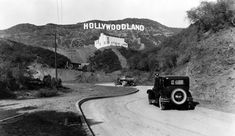 """The Hollywood Sign originally read """"HOLLYWOODLAND"""".  When those white, sans-serif block letters first rose from Mount Lee in 1923, it was a real-estate ad, not a cultural symbol. The 13 letters illuminated by 4,000 incandescent bulbs promoted the Hollywoodland subdivision to the rest of  LA. The designers scaled the letters 50 ft tall by 30 ft wide to be read by car. A new sign was erected in 1949 truncated to """"Hollywood"""" by the Chamber of Commerce, who felt it a fitting nickname for…"""