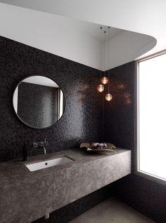 schwarze Mosaikfliesen an der Wand und Waschtisch in Steinoptik