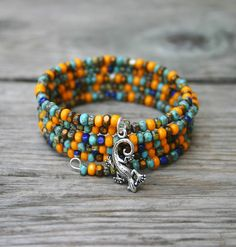 This bracelet features a mix of pretty tri-cut glass seed beads in sunflower yellow, turquoise, and blue that have been strung onto 5 coils of silver memory wire. A very cute little silver lizard charm has been added to complete this southwestern-themed bracelet. The bracelet is