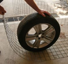 Curved gabion wall. Bending the wire mesh into a curve around the car's spare wheel.