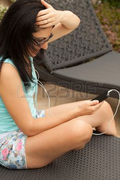 Young brunette Caucasian woman sitting on sunbed in the garden and messaging with smartphone. Stock Photo