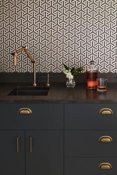 Chic black bar features black flat front cabinets and drawers adorned with thin brass pulls and brass cup pulls paired with a black countertop fitted with a square bar sink and a copper adjustable faucet.