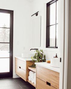 Bathroom with dark tile and oak vanities