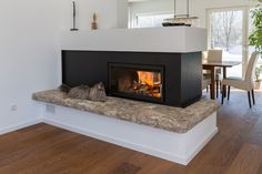 Moderner Durchsichtkamin mit Naturstein Feuerbank. #Durchsichtkamin #Tunnelkamin #Raumteiler #Ofen #Heizkamin #fireplace #Kamin #Naturstein #Feuer #Wärme #Holz #Katze #Ofenkunst #Riederinger Hafnerei