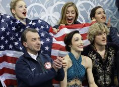 Meryl Davis, centre, and Charlie White of the United States, right, wait in the results area after competing in the team free ice dance figu...
