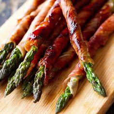 Precalienta el horno a 170º y engrasa una bandeja. Hornea espárragos durante 5 min y espolvorea con sal, pimienta y aceite verde. Retira y deja enfriar, envuelve en tiras de jamón y hornea durante 10 min.   Receta:chefluigi