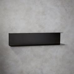 Shop bent metal black wall shelf.   Sleek steel ledge with black zinc finish elevates everything from books to barware.  Minimalist two-tier design hosts larger objects bottom, smalls up top. Pick up tips for decorating with black and white on .