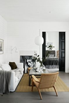 Amazing living room design with white walls, white couch and black&white photo art