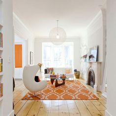 Love the geometric rug and the white sofa sitting in front of the bay window