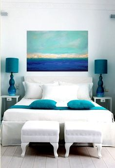 Bedroom decor ideas - blue, green and white coastal beach inspired bedroom with all white bedding and dark turquoise accents, gorgeous surreal artwork above bedding and a pair of twin benches at the foot of the bed. Greek island inspired.
