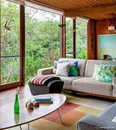 Sala de estar iluminada e com móveis sem frescura para que o filho do casal possa se divertir à vontade.