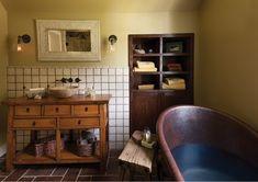 Farmhouse Bathroom. Rustic Bathroom. Bathroom stool, built-in shelves, built-in storage, console vanity, metal tub, tile floor, wall mount faucet, wall sconce, white mirror frame,  white tile backsplash, wood stool.