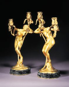 'OBSESSION' AND 'RÊVE', A PAIR OF GILT BRONZE CANDELABRA CAST FROM A MODEL BY MAURICE BOUVAL, CIRCA 1898 each of an art nouveau maiden emerging from swirling base, supporting scrolling vines terminating in sconces cast as irises, on shaped mottled black and green onyx bases.