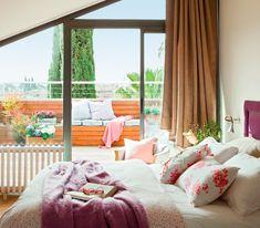 Dormitorio con salida a la terraza con ropa de cama en blanco y rosa, cojines estampados con flores. Exterior, banco revestido en madera con cojines