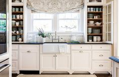 Against thecream color, the kitchen's textures really pop: the glossy countertops, the soft linen drapery, the fibrous rug.