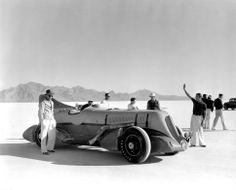 Ab Jenkins sits behind the wheel of his original Mormon Meteor, the landspeed record car that raced the Bonneville Salt Flats in 1937, with Ab's son Marv stands by the tail fin. (Photo courtesy Price Museum of Speed)