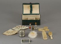 Carmel Doll Shop-Doll Trunk, deluxe green (a rare color) leather fashion Necessaire with a fitted, paper-lined interior. Housed inside is an assortment of toilette articles that includes ox bone handled brushes – including a toothbrush, hairbrush etc., a silver metal lidded receptacle complete with face powder inside, a swans down puff, a mirror, an assortment of glass bottles for toilet water, a crochet (?) hook, a fan and a hankie  $2,250.00