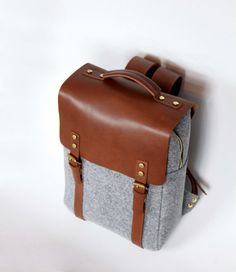 Backpack made of high quality full grain leather and felt.  Closes on the zip and buckles.  It has got regulated shoulder straps.  Outside dimensions: 40cm x 28cm x 13cm  Max. laptop size: 37,5 cm x 27 cm You can also have it with additional removable Laptop Sleeve with a pocket and a key string (you can see it in the last picture), which can be made with your name (up to 10 letters). To order the sleeve please use a variation option.   All products are handmade in our manufacture in Poland…